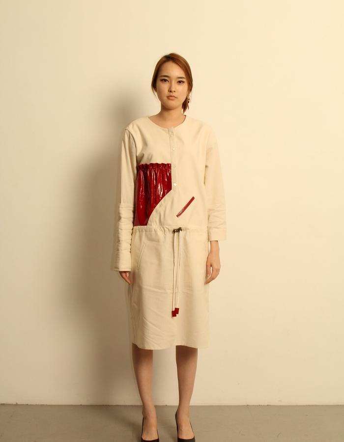 Organic cotton drawstring dress with red patent leather panel.